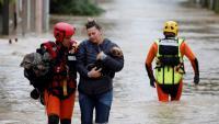 Un bomber ajuda una dona i el seu gos a travessar un carrer de Vilagalhenc inundat per l'huracà Leslie