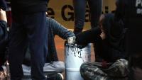 Dues persones amb les mans en un bidó de ciment, durant el desallotjament de Ca la Trava