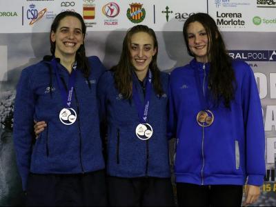 Lidón Muñoz , flanquejada per Marta González, a l'esquerra, i Ainhoa Campabadal en el podi de 100 m lliure