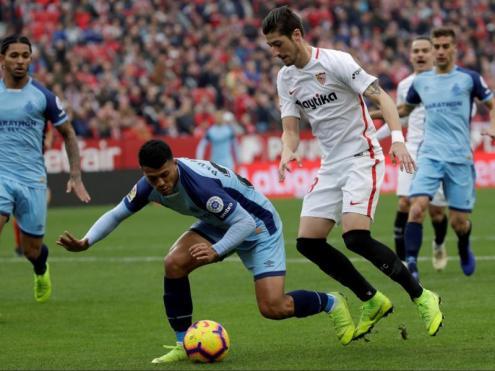 El jugador del Girona Pedro Porro cau pugnant per una pilota amb  el sevillista Sergio Escudero