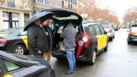Uns taxistes s'arreceraven ahir de la pluja, durant la protesta a la Gran Via