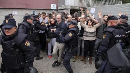Gent amb les mans alçades davant la Policia Nacional l'1 d'octubre de 2017 en un col·legi electoral de Girona
