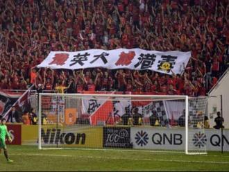 """A dalt, els seguidors xinesos del Guangzhou Evergrande mostren una pancarta amb el lema """"Aniquilem els gossos britànics, eliminem la independència de Hong Kong"""". A baix, protestes mentre sona l'himne xinès"""