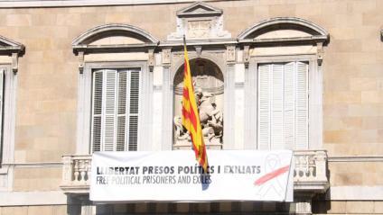 """""""Llibertat presos polítics i exiliats"""", diu la nova pancarta amb un llaç blanc amb una franja vermella, en comptes del llaç groc de la pancarta anterior, a la façana del Palau de la Generalitat"""