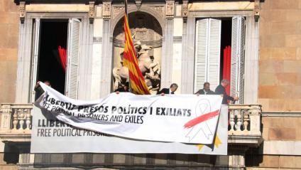 Moment en què col·loquen la nova pancarta sobre l'antiga amb el llaç groc, al palau de la Generalitat
