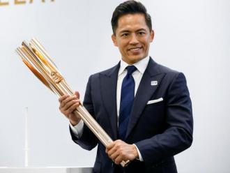 Tadahiro Nomura, tricampió olímpic de judo, mostra la torxa de Tòquio