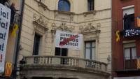 Els veïns en el moment que penjaven la pancarta –avui retirada– als seus balcons davant la façana de l'Ajuntament