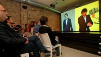 Sànchez i Puigdemont conversant per videoconferència des de Waterloo i Soto del Real, seguits per dirigents de JxCat a la seu de la formació