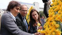 Quim Torra, la seva esposa i Txell Bonet dipositen roses grogues al mural d'Òmnium Cultural
