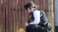 Una policia , divendres, deixa un ram de flors al lloc on havia caigut abatuda el dia abans Lyra McKee