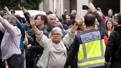 Una senyora aixeca els braços davant la policia espanyola l'1 d'octubre, en una imatge d'arxiu