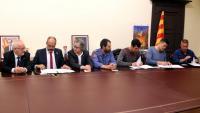 El conseller d'Interior, Miquel Buch, i els sindicats de Bombers signant l'acord