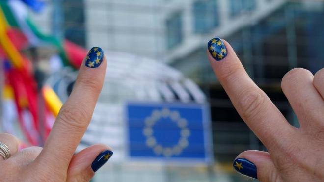Una dona mostra les ungles pintades amb els colors de la bandera de la UE davant del Parlament Europeu a Brussel·les