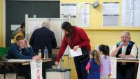 Una dona introdueix el vot a l'urna en un col·legi electoral de Dublín en les eleccions celebrades divendres a Irlanda