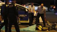 El repartidor, amb la bossa de Glovo, estirat a terra i equips d'emergències i de la Guàrdia Urbana aquesta nit a la Gran Via de Barcelona