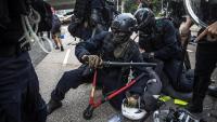 La policia antiavalots deté uns dels manifestants, enmig d'una batalla campal