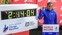 Brigid Kosgei al costat del marcador que reflecteix el nou rècord mundial