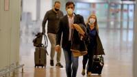 Uns viatgers amb mascareta sortint de la zona de recollida de maletes del Prat