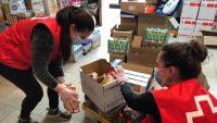 Dues voluntàries de Creu Roja preparant un lot d'aliments