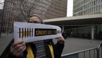 Una persona mostra un cartell de suport al síndics de l'1-O