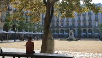 Una persona asseguda sola en un banc a Girona