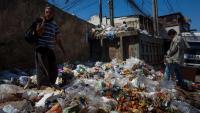 Dos homes busquen menjar en un abocador de brossa a la ciutat de Caracas (Veneçuela)