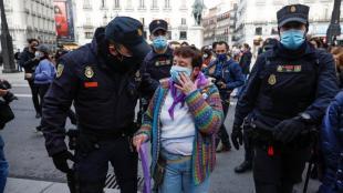 Agents de la policia espanyola acompanyen la dona que ha patit ferides durant la concentració a la Porta del Sol de Madrid