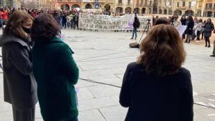 En primer terme l'alcaldessa de Vic, Anna Erra, i altres regidores i al fons la protesta per l'hort urbà que l'ajuntament ha desmuntat de matinada
